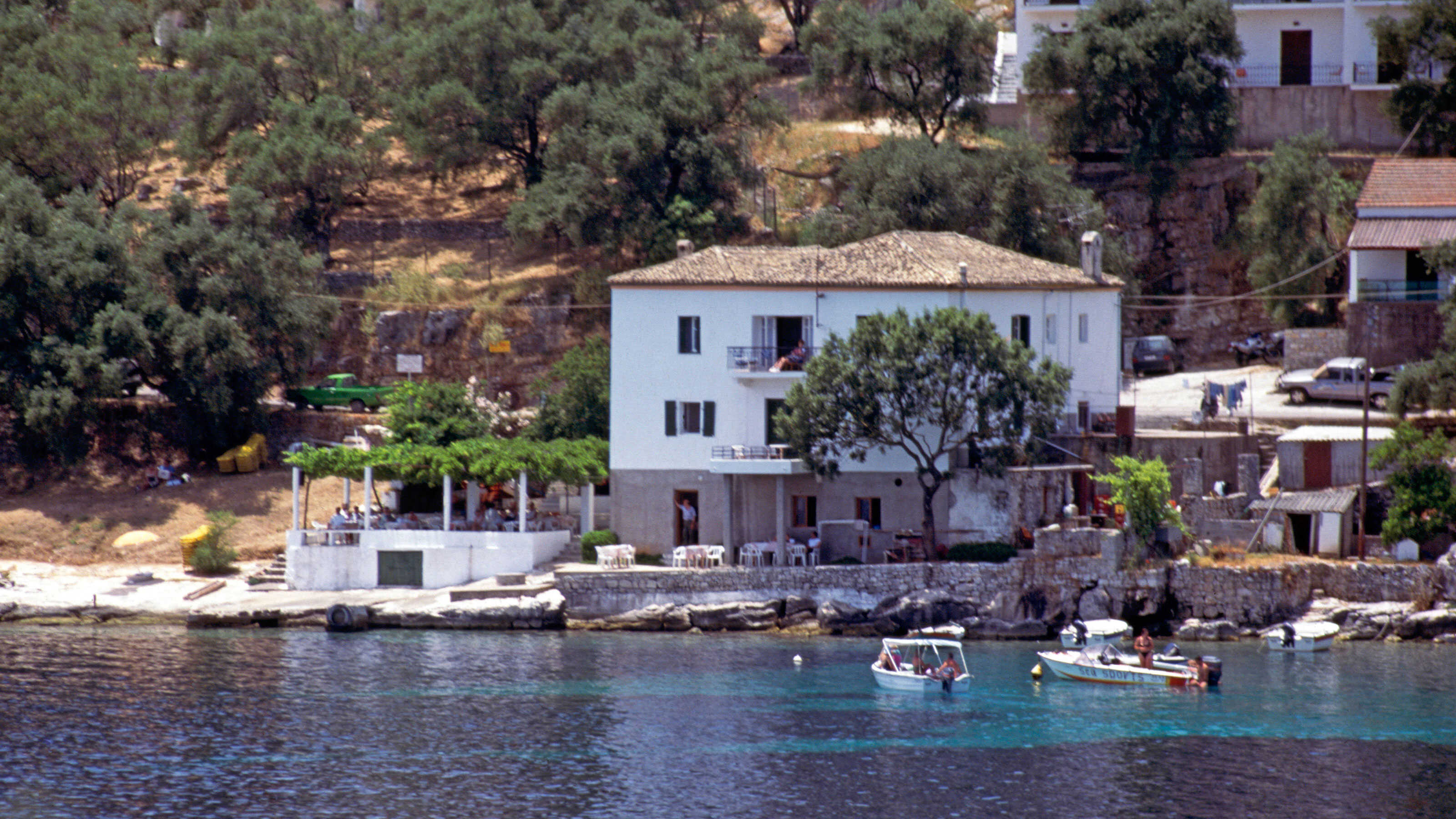 A few pleasure boats moored in the clear waters in front of the pebble beach of Kalami on the island of Corfu a tree in front of Lawrence Durrell s White House where he wrote Prospero s Cell .